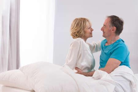 ベッドで一緒に幸せな先輩カップルの肖像画