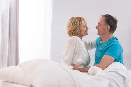 a pair of: Portrait Of Happy Senior Couple Together In Bed