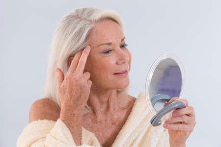 彼女のしわを示す鏡で自分自身を見ている熟女