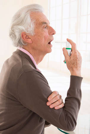 asthmatic: Senior man feels pain in the throat - Applaying medical spray