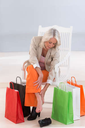 woman foot: senior woman sitting on a chair surrounded by shopping bags and rubbing her sore feet.