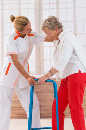 giver: Care giver helping elderly woman to walk with a walker