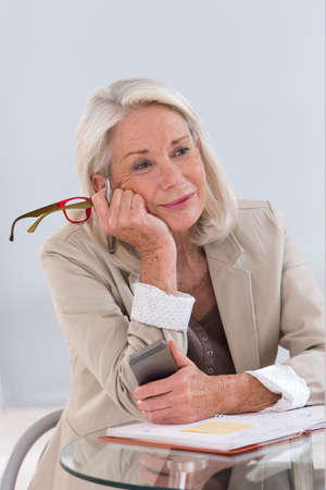 woman on phone: Portrait of smiling mature businesswoman with eyeglasses