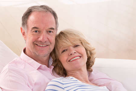 contented: Romantic Mature couple sitting close together on a sofa in their living room in a loving embrace smiling at the camera