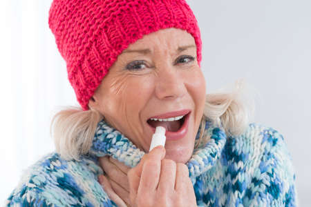 balm: Attractive Senior woman applying lip balm Stock Photo