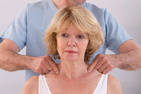 spinal conditions: Doctor massaging his patient neck in medical office