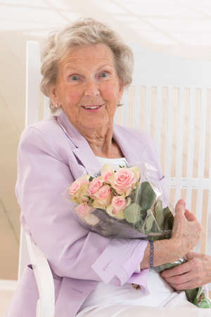 elderly woman: Happy attractive senior woman with a bunch of flowers Stock Photo