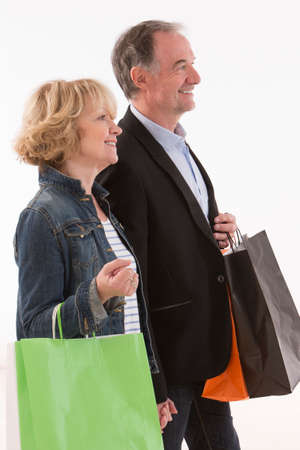 shot: Happy Mature Couple Holding Multi Colored Shopping Bags Stock Photo