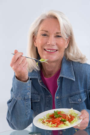 Caucasian woman: Senior woman eating a healthy salad at the kitchen