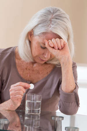 suffers: Senior woman suffers from headache, sitting at table with pills and glass of water Stock Photo