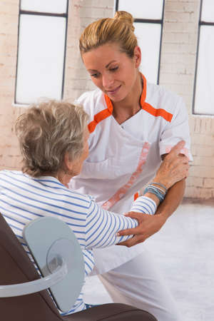 a lady doctor: Careful female caregiver helping senior woman to stand up