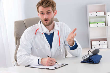 patient in hospital: young male doctor in his office