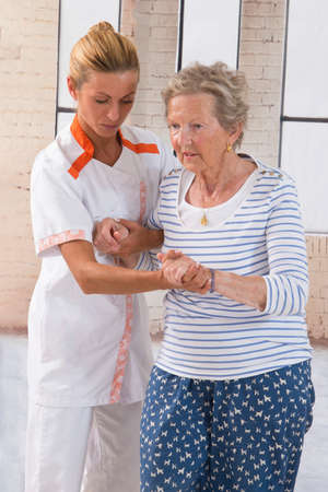 elderly woman: Careful female caregiver helping senior woman to stand up