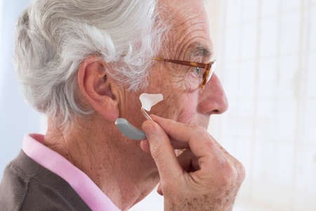Closeup of a senior man inserting a hearing aid in her hear