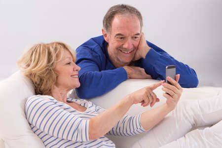 couple talking: Happy mature couple using smartphone together at home in living room
