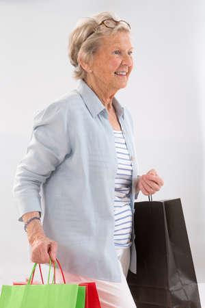 compras compulsivas: Feliz mujer Compras ancianos. Aislado sobre fondo gris Foto de archivo