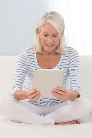 android tablet: Portait of senior woman using electronic tablet at home