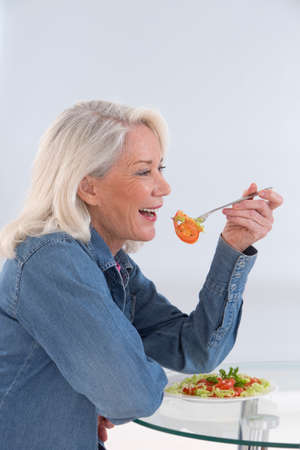 one senior adult woman: Senior woman eating a healthy salad at the kitchen