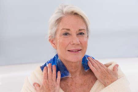 年配の女性の首にゲルのパックを入れて 写真素材