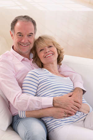 living together: Romantic Mature couple sitting close together on a sofa in their living room in a loving embrace smiling at the camera