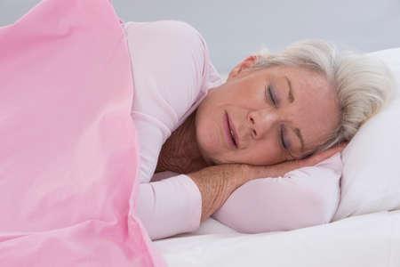 Mulher sênior que dorme na cama