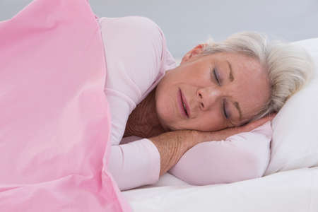 one senior: senior woman sleeping on bed