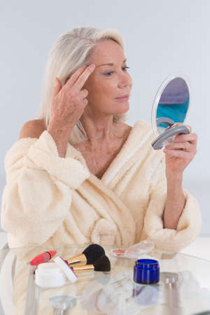 only women: Mature woman looking at herself in the mirror showing her wrinkles