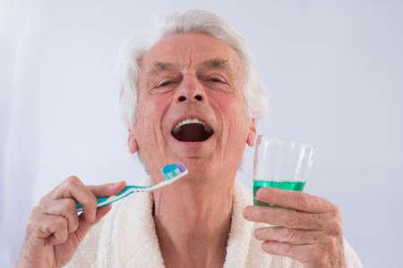 enjuague bucal: thooth hombre mayor que sostiene cuidadosamente los dientes cepillo y enjuague bucal en un vaso Foto de archivo