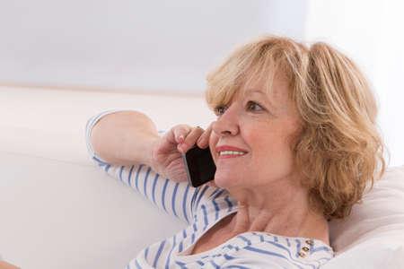 senior woman: Senior woman using smartphone, in living room