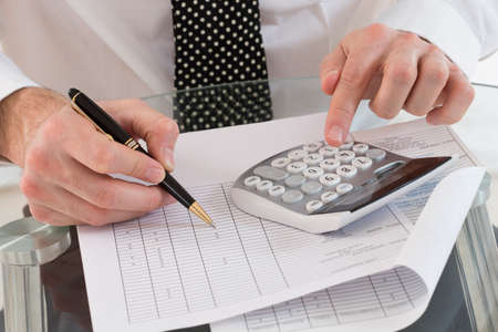 Accountant: image of businessman using calculator in office Stock Photo
