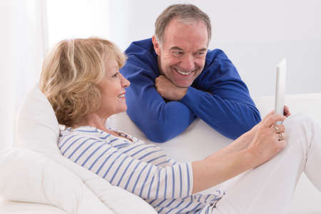 couple relaxing: lovely mature couple using tablet computer at home