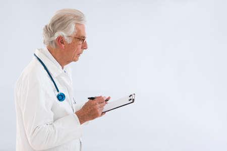 bata blanca: médico reflexivo whritting en el portapapeles