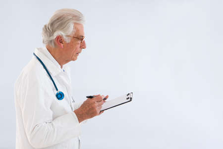 white coat: thoughtful doctor whritting on clipboard