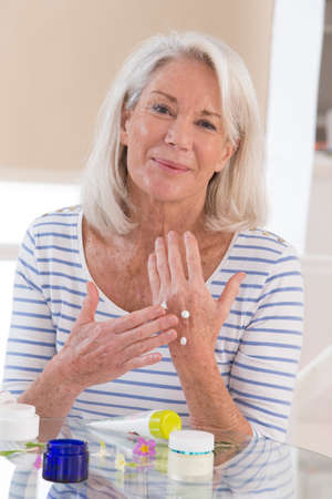 Smiling senior woman applying cream on her hands Stock Photo