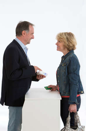 medicalcare: Senior woman talking with male pharmacist Stock Photo