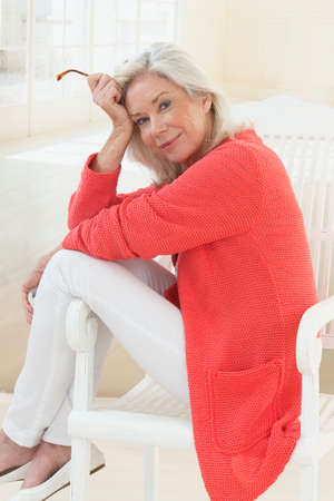 profil: Senior Woman Relaxing In Chair At Home Reading Book