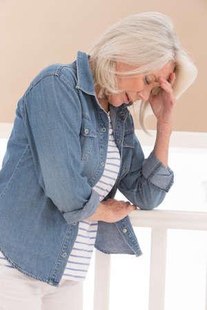 depresión: Mujer mayor que tiene headacche