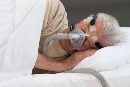 SLEEP APNEA SYNDROME -Senior man using CPAP machine Stock Photo