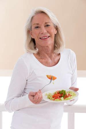 mujeres maduras: Mujer mayor que come una ensalada saludable en la cocina Foto de archivo