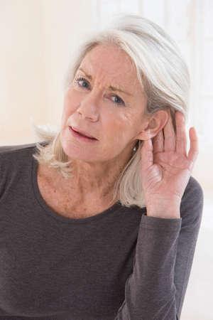 Oudere vrouw met hardheid van hoor zitting te luisteren