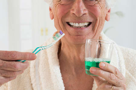 thooth care- senior man holding teeth brush and mouthwash in a glass Stock Photo