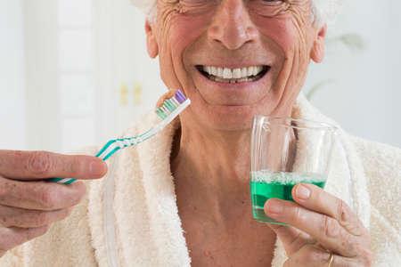thooth zorg- senior man houden tanden borstel en mondwater in een glas
