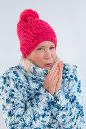 shiver: portrait of freezing senior woman wearing winter clothe and hat