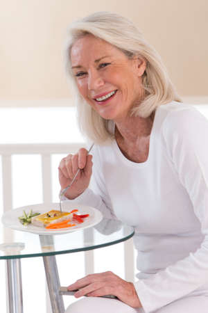 70s adult: Senior woman eating a healthy salad at the kitchen