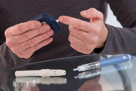 blood sugar: hands of senior with utensils of blood sugar test Stock Photo