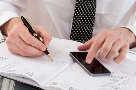man s: Image of  business man s hands plan ning on agenda book, and smartphone  in office