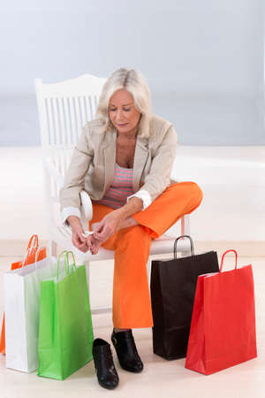 senior woman sitting on a chair surrounded by shopping bags and rubbing her sore feet.