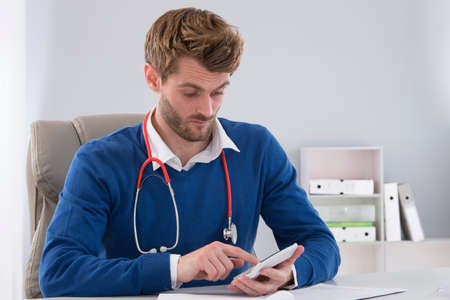physican: doctor with a calculator. calculation of costs and revenues Stock Photo