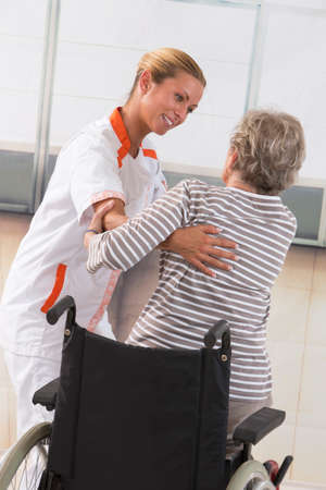 aucasian: Careful female caregiver helping senior woman to stand up