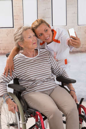 aucasian: Young nurse taking a selfie to ensure the family about the good condition of the grandmother.